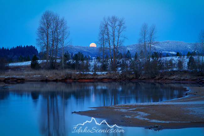 Idaho, North, Silver Valley, Cataldo. A full moon setting behind a ridge in the Coeur d'Alene Mountains before sunrise in winter.