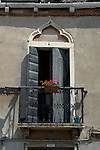 Venetian balcony with simple flower box of geraniums and watering can. Venice. Italy.