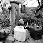 Richard Saunders gathers abandoned gasoline canisters, used by human traffickers, in the desert near North Komelik, AZ, on Sunday, July 13, 2008.