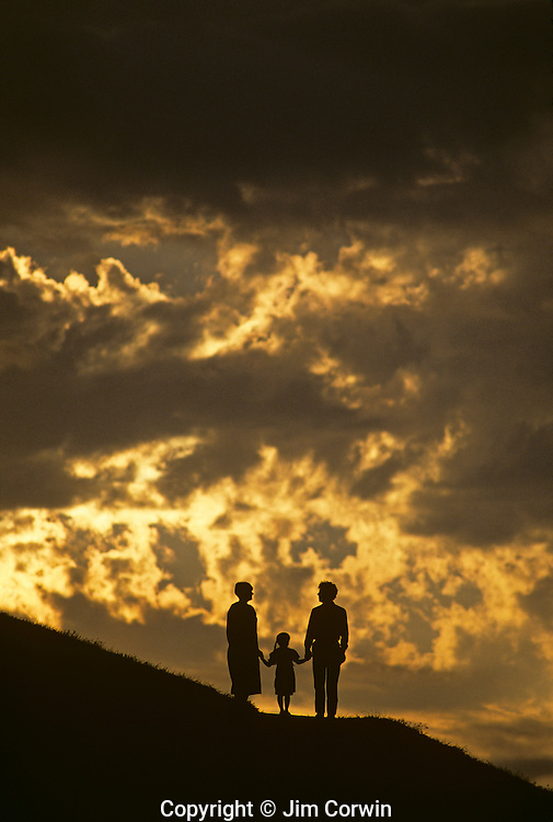 Family on hillside holding hands and facing life together.
