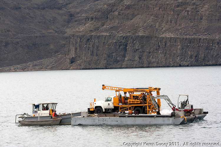 A drilling crew from the Grant County Public Utility District hauls a barge loaded with a truck and mini excavator on the Columbia River at the Frenchman Coulee landing just north of the Wanapum Dam in Washington on February 8, 2011.  The crew will perform an overwater geotechnical investigation taking soil samples which will be used to design pilings for a boat launch. (photo credit Karen Ducey)