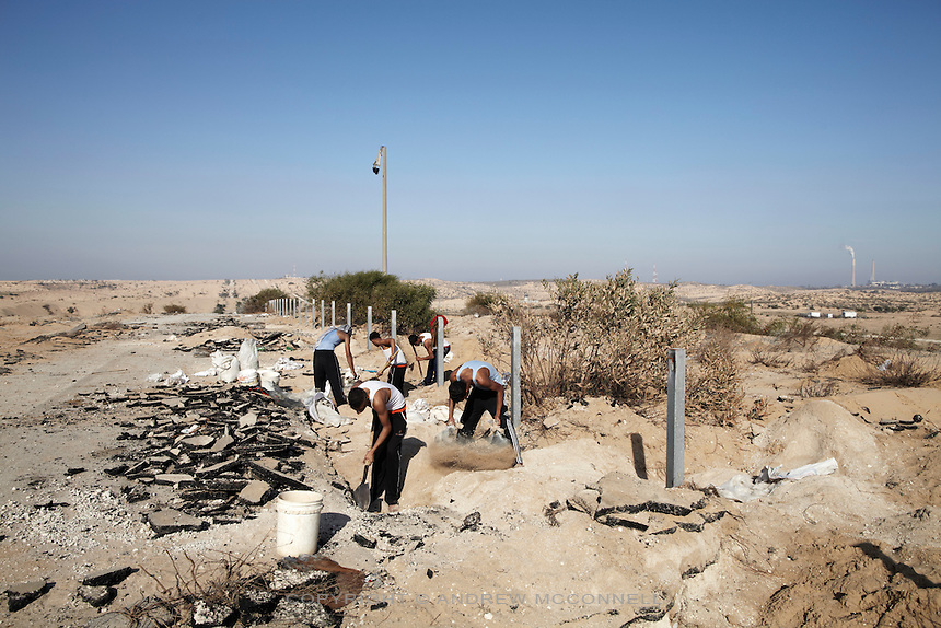 Teenagers searching for gravel dig under an old settlement road running parallel to the Israel border, which is a mere 50 meters away. Many Palestinians have been shot in this area while gathering building materials.
