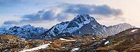 Stornappstind (740m) mountain peak rises above dramatic landscape, viewed from Offersoykammen, Lofoten Islands, Norway