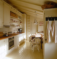 Traditional country furniture, painted to match the rest of the decor, fills this simple contemporary Norwegian kitchen
