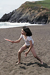 Girl, 10-yrs-old, demonstrating good athletic form while playing frisbee on a California beach (1/2 Latina)