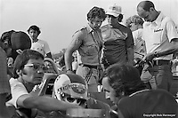 INDIANAPOLIS, IN: Clay Regazzoni sits in his McLaren M16C 4/Offenhauser TC while Mario Andretti (center, standing) inspects the car before practice for the Indianapolis 500 on May 29, 1977, at the Indianapolis Motor Speedway.