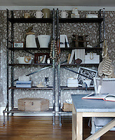 The crewelwork fabric on the walls of the study is a great background for a set of industrial shelves from an old Polish factory