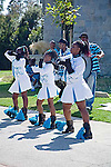 African American teen girls perform drill team routine outdoors with boys playing musical instruments