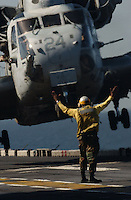 A flight director on the carrier USS Bataan signals the super stallion helicopter to proceed as it hovers away with U.S. Marines bound for the war zone in Afghanistan.
