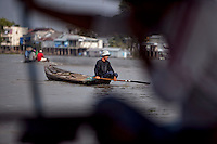 "Sa, 45, looks for the right current to cast out his fishing net on the Hau Giang River, a tributary of the Mekong River, in Chau Doc, in the An Giang Province, Vietnam. When the Mekong River reaches Vietnam it splits into two smaller riveres. The ""Tien Giang"", which means ""upper river"" and the ""Hau Giang"", which means ""lower river"". Photo taken on Monday, December 7, 2009. Kevin German / Luceo Images"