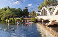 Standup paddleboarders near Anahulu Stream Bridge in Haleiwa, O'ahu.