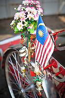 The Malaysian flag flying on the side of the traditional bicycle rickshaw of Penang, Malaysia.