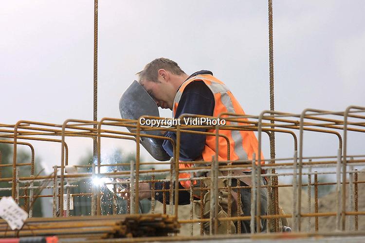 Foto: VidiPhoto..EDE - In Ede-West wordt gebouwd aan het breedste viaduct van Nederland. De tuibrug over de A12 wordt 50 meter breed en 100 meter lang. Behalve vier rijstroken, komen er ook twee busbanen en twee fietspaden. De nieuwe verbinding is onder meer nodig door de bouw van een nieuwe wijk, ziekenhuis en winkelcentrum in Ede-West, waardoor het verkeer tussen Ede en de A12 enorm is toegenomen tot 1 miljoen verkeersbewegingen per jaar. Ambulances van en naar het nieuwe ziekenhuis  liep daardoor soms vast in het verkeer. Het viaduct moet begin 2003 gereed zijn.