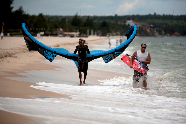 Scott Soothill, owner of STORM Kiteboarding, and Binh walk back with their kite after attempting the first ride of the day on Mui Ne beach.  Low winds grounded them for the rest of day.