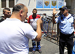A Palestinian man argues with an Israeli policeman as others take part in Friday noon prayers in the east Jerusalem neighbourhood of Ras al-Amud on July 31, 2015, following restrictions by Israeli police to allow entry to men only above 50-year-old wanting to access the Al-Aqsa Mosque compound. Photo by Saeb Awad