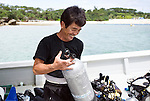 Fisherman Munekazu Mekaru, who set into life a coral reef restoration project, loads dive equipment onto his boat before a dive to bolt pieces of coral to the sea floor in the bay at Onna Village, Okinawa Prefecture, Japan, on Saturday, June 23, 2012. Photographer: Robert Gilhooly
