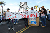 Mesa, Arizona. February 23, 2012 - As Republican candidates debated in the Mesa Arts Center, protesters including undocumented students, tea partiers, occupy movement members and Syrian president opponents, shouted slogans and held up signs and placards outside. In this photograph, youth members of the Arizona-based Tequila Party hold a banner showing their opposition to Republican presidential candidate Mitt Romney. Photo by Eduardo Barraza © 2012
