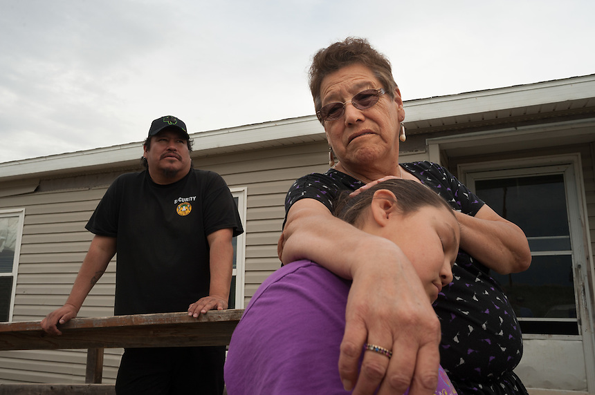 Overcrowding is rampant on the Crow Reservation at Crow Agency, Montana, where 13 people from three families live on double-wide mobile home, including Thomas Bad Bear, left, Shirley Bad Bear and Tillie Davis, 10, Thursday, May 16, 2013. Pending new ports for shipment to Asia through either the U.S. or Canada, Cloud Peak Energey hopes to open new high-grade coal mines on and near the Crow Reservation in southern Montana. The tribe is equally hopeful the new mines would bring long-awaited economic stability to the tribe. (Kevin Moloney for the New York Times)