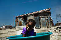 A Haitian kid play with waste water in the slum of Cité Soleil, Port-au-Prince, Haiti, 11 July 2008. Cité Soleil is considered one of the worst slums in the Americas, most of its 300.000 residents live in extreme poverty. Children and single mothers predominate in the population. Social and living conditions in the slum are a human tragedy. There is no running water, no sewers and no electricity. Public services virtually do not exist - there are no stores, no hospitals or schools, no urban infrastructure. In spite of this fact, a rent must be payed even in all shacks made from rusty metal sheets. Infectious diseases are widely spread as garbage disposal does not exist in Cité Soleil. Violence is common, armed gangs operate throughout the slum.