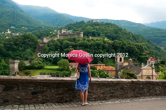 A view of two of three castles in Bellinzona, Switzerland including a view of the Church of Saint Peter in downtown Bellinzona. A woman looks at the view of Bellinzona, Switzerland while holding an umbrella in the rain