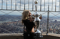 """New York, USA. 23 April 2014.  """"Miss Supercross"""" Dianna Dahlgren, kisses the trophy as she promotes the motorcycle race during a visit to the Empire State Building in New York. Photo by Eduardo Munoz Alvarez/VIEWpress"""