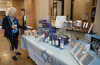 NWA Democrat-Gazette/J.T. WAMPLER  Beth Nodelman of Fayetteville points out items for sale Sunday Nov. 23, 2015 at Temple Shalom of Northwest Arkansas. The Fayetteville temple sets up a shop each year, selling gifts for Hanukkah, some of which are imported from Israel.
