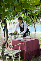 A waitress puts the finishing touches to a table laid for lunch in the vineyard