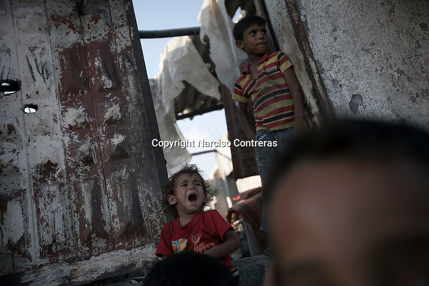 "In this Saturday, Aug. 16, 2014 photo, Palestinian children are seen at the entrance of their house after it was damaged by artillery shelling during the ""Protective Edge"" Israeli military operation in Beit Hanoun neighborhood in Gaza City. After a five days truce was declared on 13th August between Hamas and Israel, civilian population went back to what remains from their houses and goods in Gaza Strip. (Photo/Narciso Contreras)"