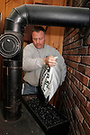 TERRYVILLE, CT05 January 2006-010506TK04 Chris Wald, owner of Back To Basics store in Terryville, adds  coal burning granules used to a coal stove that warms his Terryville business.   Tom Kabelka / Republican-American (Chris Wald, coal)CQ