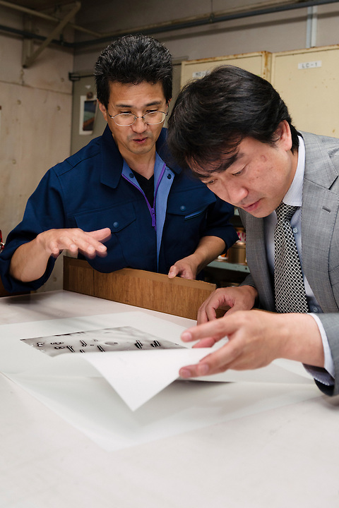 Head printer Osamu Yamamoto (left) and CEO Takumi Suzuki discuss a collotype print by photographer Antony Cairns. Benrido collotype atelier, Kyoto, Japan, October 13, 2015. The Benrido collotype atelier in Kyoto was founded in 1887 and is the only full-scale commercial collotype atelier in the world. Collotype is a historic photographic printing process that makes use of plates coated in gelatine. It produces prints of unrivalled quality.