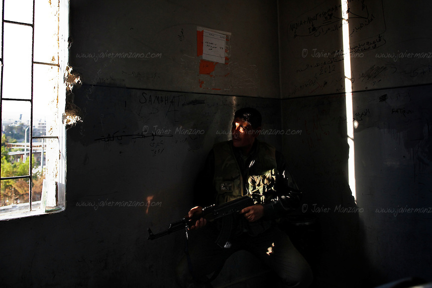 A Free Syria Army soldier moves into position to fire at loyalist positions in the Bustan Al-Bashar neighborhood of Aleppo on the last day of a U.N.-negotiated seize fire that began on the first day of the Muslim holiday of Eid. Both sides exchanged small arms fire as the regime fired mortars throughout the day on several sectors of the city - the kurdish neighborhood of Ashrafya was also bombed by regime jets on October 29, 2012, following an FSA incursion in the district on Saturday...© Javier Manzano......................................................