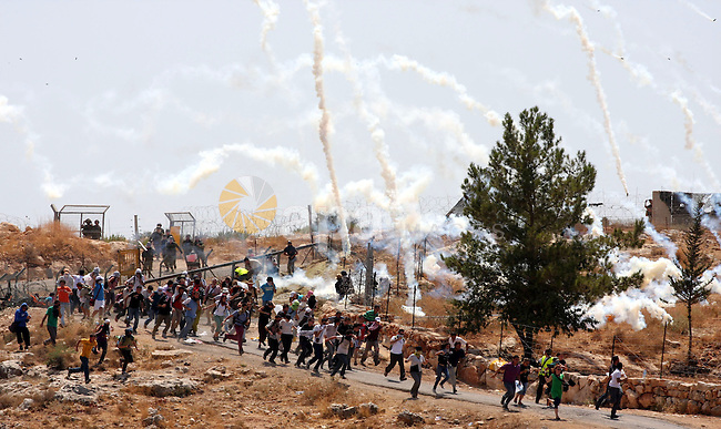 Palestinian and foreign protesters run to cover from tear gas fired by Israeli soldiers during a demonstration against Israel's controversial separation barrier in the West Bank village of Bilin near Ramallah on July 31, 2009. Photo by Issam Rimawi