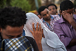 Eritrean migrants in Tel Aviv, Israel, cry during a memorial ceremony for Haftom Zarhum, a 29 year-old Eritrean migrant who was shot by security men and then lynched by an Israeli mob. Three days earlier, after a Palestinian gunman fatally-attacked Israelis in the southern city of Be'er Sheva, Haftom Zarhum was mistakingly thought to be the Palestinian attacker by a security man.
