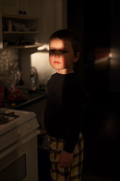 My younger son stands on a kitchen stool, threatening to turn off the microwave timer because he doesn't want to have a time-out.