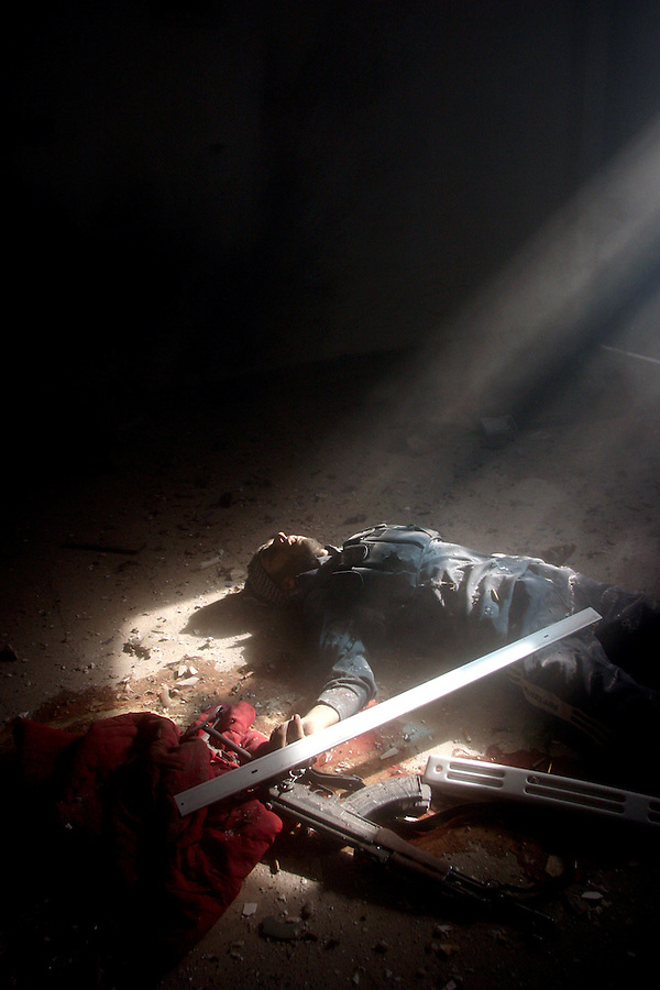 The body of an insurgent lies on the floor of a home in western Fallujah after Marines with Kilo Co. (3/1) discovered him and two companions while searching city blocks house by house on Saturday, Nov. 13, 2004.  The death of the trio was only the beginning of a firefight in the house that lasted more than an hour and left one Marine and seven insurgents dead. Seven Marines were seriously wounded as Kilo Co. struggled to evacuate its casualties under fire.  Finally able to exit the building, combat engineers leveled the structure with 20 lbs. of high explosives in an effort to kill any fighters remaining inside. The fight in the home became known as the ?Hell House? to Kilo Co. and marked a turning point in the way the company cleared the rest of their piece of the city. Afterward, when contact was made with the insurgents, the Marines called in bulldozers, C-4, and air strikes.