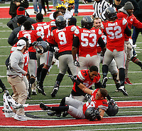 Ohio State Buckeyes running back Jordan Leasure (28) and Ohio State Buckeyes safety Erick Smith (34) celebrate at midfield as players react to a 30-27 win over Michigan in double overtime during Saturday's NCAA Division I football game at Ohio Stadium in Columbus on November 26, 2016. (Barbara J. Perenic/The Columbus Dispatch)