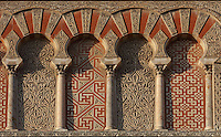 Architectural detail of the Puerta de San Jose, one of the East facade entrances to the Cathedral-Great Mosque of Cordoba, on the Calle del Magistrado Gonzalez Frances in Cordoba, Andalusia, Southern Spain. This section includes horseshoe arch niches, with miniature columns and capitals, red brick, mosaic work and intricately carved vegetal patterns. The Moorish gate is named after St Joseph, whose chapel is on the other side of the door, and was restored in 1913 by Ricardo Velazquez Bosco. The first church built here by the Visigoths in the 7th century was split in half by the Moors, becoming half church, half mosque. In 784, the Great Mosque of Cordoba was begun in its place and developed over 200 years, but in 1236 it was converted into a catholic church, with a Renaissance cathedral nave built in the 16th century. The historic centre of Cordoba is listed as a UNESCO World Heritage Site. Picture by Manuel Cohen