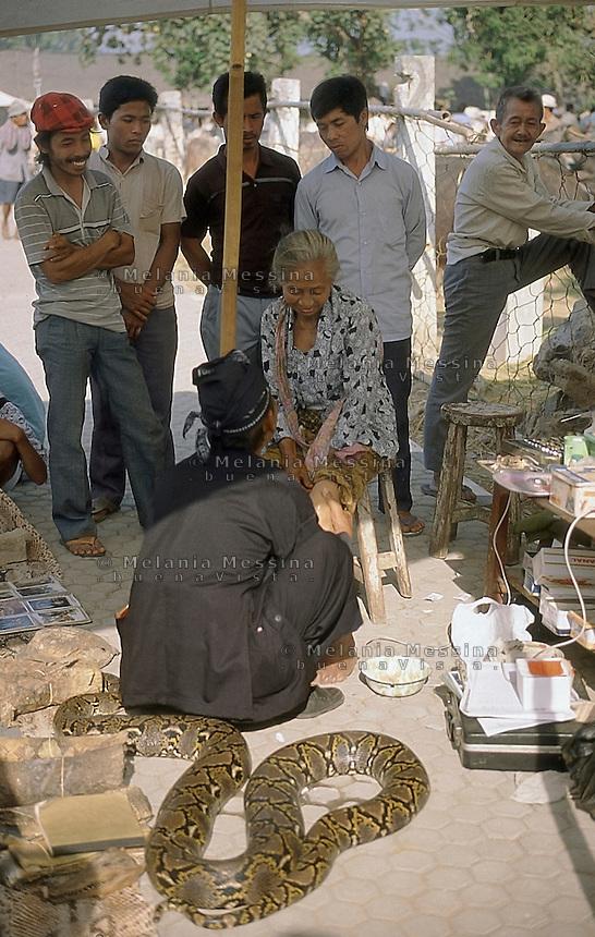 Indonesia, Java island : the Dukun (healer)Pak Iwo massages a patient to heal her pain.<br /> Indonesia, Giava: il dukun (guaritore) Pak Iwo massaggia una sua paziente per guarirla dai dolori.