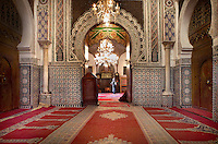 Low angle view of interior, with doorway to sanctuary, Moulay Idriss II Mosque, Fez, Morocco, pictured on February 21, 2009. The Mosque of Moulay Idriss II (reigned  803-828), was built by the Idriss dynasty and restored in the 13th century by the Merenids. Containing the mausoleum of Moulay Idriss II, who is believed to aid women's fertility, it is an important pilgrimage destination and a  zaouia or sanctuary. Across the entrance a wooden beam excludes Jews, Christians, and donkeys from the horm, or sacred area around the shrine, where  Moroccans may historically claim sanctuary from arrest. The tomb, covered in brocade and surrounded by the faithful burning candles and incense, is visible through the doors, worn smooth by centuries of pilgrims kissing the wood for baraka or blessing. Fez, Morocco's second largest city, and one of the four imperial cities, was founded in 789 by Idris I on the banks of the River Fez. The oldest university in the world is here and the city is still the Moroccan cultural and spiritual centre. Fez has three sectors: the oldest part, the walled city of Fes-el-Bali, houses Morocco's largest medina and is a UNESCO World Heritage Site;  Fes-el-Jedid was founded in 1244 as a new capital by the Merenid dynasty, and contains the Mellah, or Jewish quarter; Ville Nouvelle was built by the French who took over most of Morocco in 1912 and transferred the capital to Rabat. Picture by Manuel Cohen.