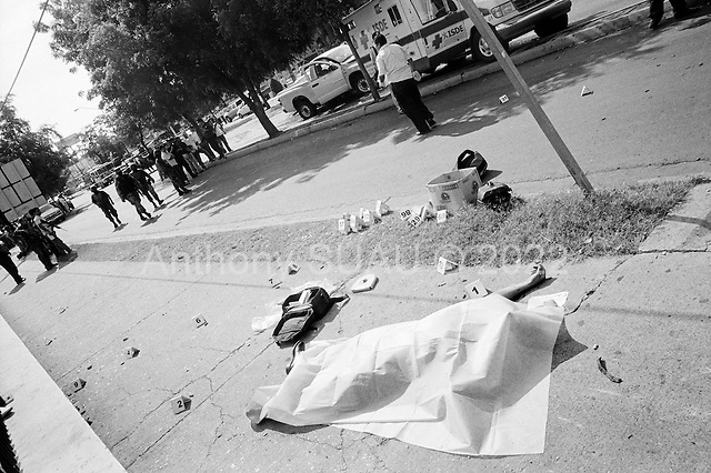 Culiacan, Sinaloa.Mexico.July 4, 2008..During Friday rush hour on main street in Culiacan three people were killed by narco gunmen, one state police commander, a state police officer and a female civilian. Over three hundred rounds on ammunition were fired on the scene. From January 1 to mid-July 2008 there have been 535 drug related killings in Sinolao, many of them were police officers...Dozens of people look on in terror at the shooting familiar to the American faces at ground zero..