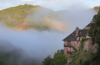 Traditional house on the edge of a valley, filled with morning mist, Conques, Aveyron, Midi-Pyrenees, France. Picture by Manuel Cohen