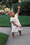 Richmond, CA African American baby twelve months old demonstrating new walking ability while using arm for balance  MR