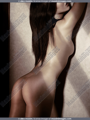 Beautiful naked Japanese woman standing leaning against the wall in dim light with shadows