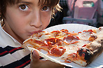An Italian boy eating pizza at the Italian Feast of San Gennaro - Los Angeles - a four day Italian festival in Hollywood, CA