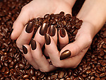 Woman holdings coffe beans in her hands with matching nail polish