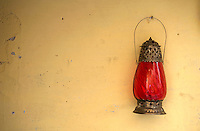 """A lamp out side a wall, Jaisalmer the old City and fort.J a i s a l m e r   J a i s a l m e r  n i c k n a m e d   """" T h e   G o l d e n   C i t y """" ,   i s   a   t o w n   i n   t h e   I n d i a n   s t a t e   o f   R a j a s t h a n .   T h e   t o w n   s t a n d s   o n   a   r i d g e   o f   y e l l o w i s h   s a n d s t o n e ,   c r o w n e d   b y   a   f o r t ,   w h i c h   c o n t a i n s   t h e   p a l a c e   a n d   s e v e r a l   o r n a t e   J a i n   t e m p l e s .   M a n y   o f   t h e   h o u s e s   a n d   t e m p l e s   a r e   f i n e l y   s c u l p t u r e d .   I t   l i e s   i n   t h e   h e a r t   o f   t h e   T h a r   D e s e r t   a n d   h a s   a   p o p u l a t i o n   o f   a b o u t   7 8 , 0 0 0 .   I t   i s   t h e   a d m i n i s t r a t i v e   h e a d q u a r t e r s   o f   J a i s a l m e r   D i s t r i c t ....Jaisalmer Fort is one of the largest of desert forts of the world. It is situated in Jaisalmer city in Indian state of Rajasthan. It was built in 1156 AD by the Bhati Rajput ruler Rawal Jaisal, from where it derives it name. The fort stands proudly admist the golden stretches of the great Thar Desert, on Trikuta Hill and had been the scene of many battles. Its massive yellow sandstone walls are a tawny lion color during the day, turning to a magical honey-gold as the sun sets and camouflages the fort making it appear a part of the picturesque yellow desert. Thus, it is also known as the """"Golden Fort"""".."""