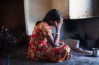 Nitu (not her real name), wipes her forehead in her kitchen in Jhaju village, Bikaner, Rajasthan, India on 4th October 2012. Now 18, she was married off at age 10 to a boy of around the same age, but only went to live with her in-laws when she was 12, after she had finished studying up to class 6. The three sisters, aged 10, 12, and 15 were married off on the same day by their maternal grandfather while their father was hospitalized. She was abused by her young husband and in-laws so her father took her back after hearing that her husband, who works in a brick kiln, was an alcoholic and was doing drugs and crime. She had only spent a few days at her husband's house at that time. Her father (now out of the hospital) has said that she will only be allowed to return to her husband's house if he changes his ways but so far, the negotiations are still underway. Photo by Suzanne Lee for PLAN UK
