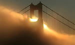 The sunrise lights up the fog as it streams through the northern tower of  Golden Gate Bridge, California.