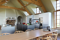 Beneath the cathedral-like oak ceiling beams of this converted barn, the wood finish of the dining area pulls together the layout of this contemporary kitchen