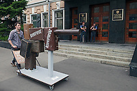 Moscow, Russia, 19/05/2012..Police guarding the Russian Federal Agency for Print and Mass Communication watch an artwork consisting of suitcases fashioned to look like a gun and bearing the work ?kompromat?, Russian jargon for compromising material, as several thousand artists and opposition activists demonstrate against Vladimir Putin by walking through Moscow transporting their artworks. The protest coincided with Museum Night, when Moscow's museums are open until midnight with special exhibitions and performances.